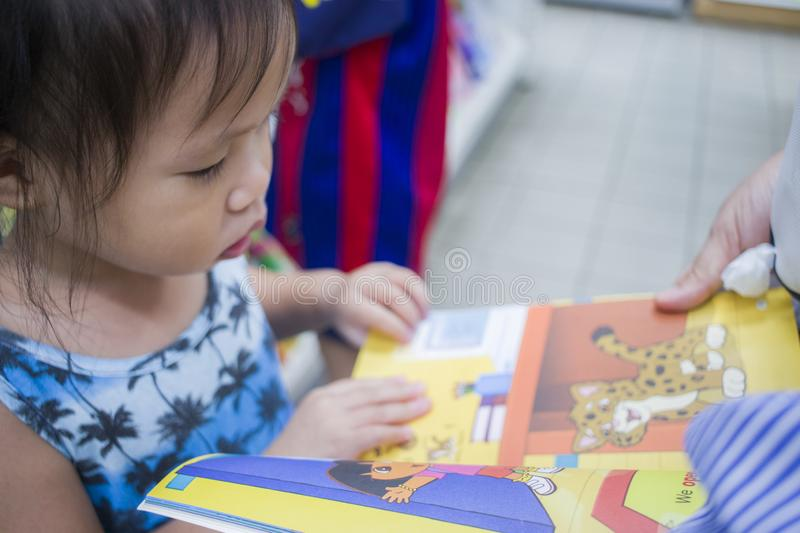 CHIANGMAI,THAILAND-MAY 3,2019 : Little Child explores the bookshelves with mom in book store royalty free stock photos
