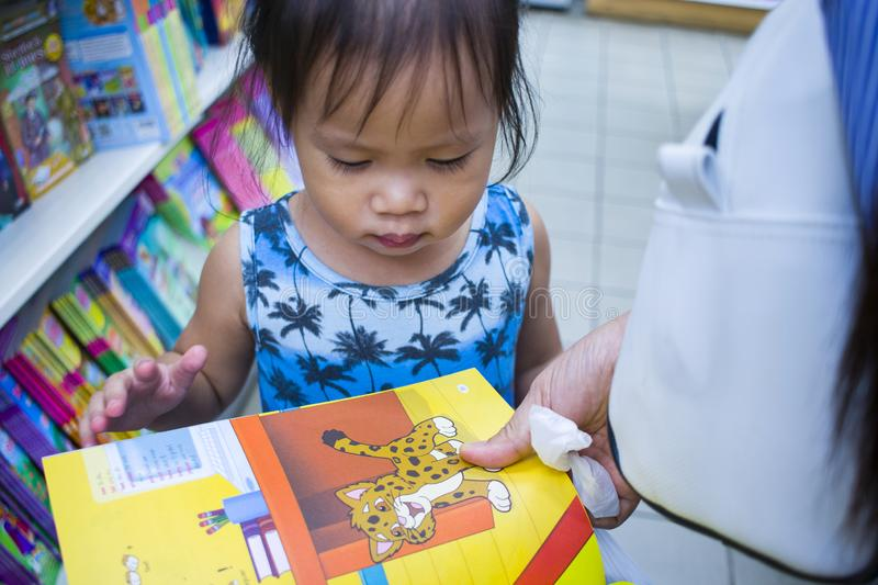CHIANGMAI,THAILAND-MAY 3,2019 : Little Child explores the bookshelves with mom in book store royalty free stock photography