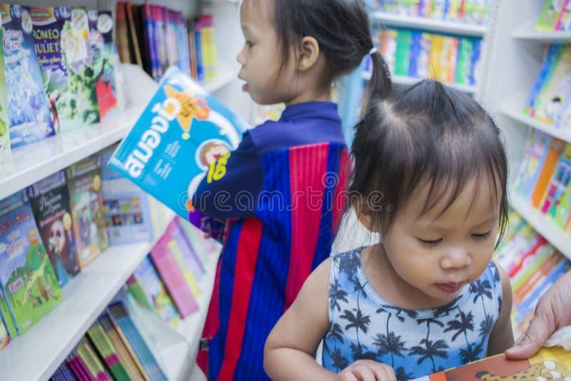 CHIANGMAI, 3,2019 THAILAND-MEI: Weinig Kind onderzoekt de boekenrekken met mamma in boekhandel royalty-vrije stock foto
