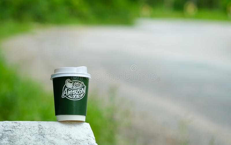 chiangmai thailand september 7 2016 amazon take away coffee cup on concrete road with blurred road background