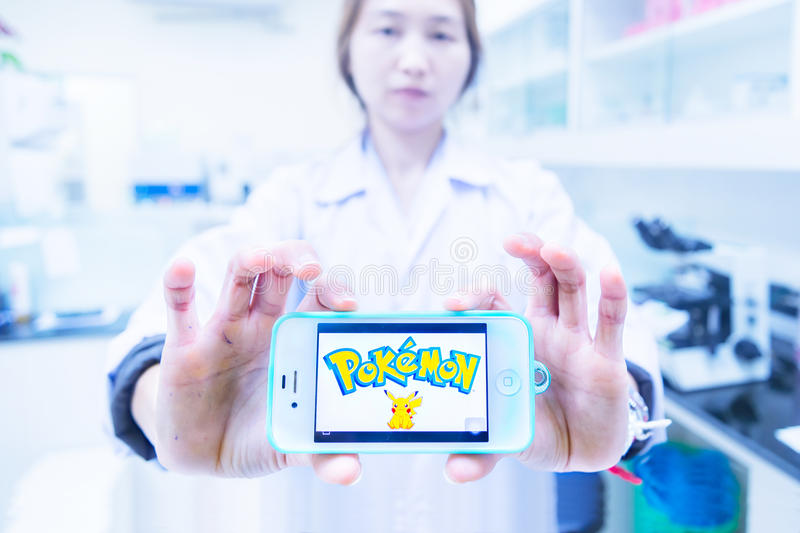 Chiangrai, Thailand - August 16th, 2016 : Asia woman medical technician holding a smart phone and show Pokemon Go logo in royalty free stock photography