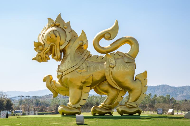 The statue of golden lion on a field with blue sky background, at Singha park Chiangrai Thailand. royalty free stock photography