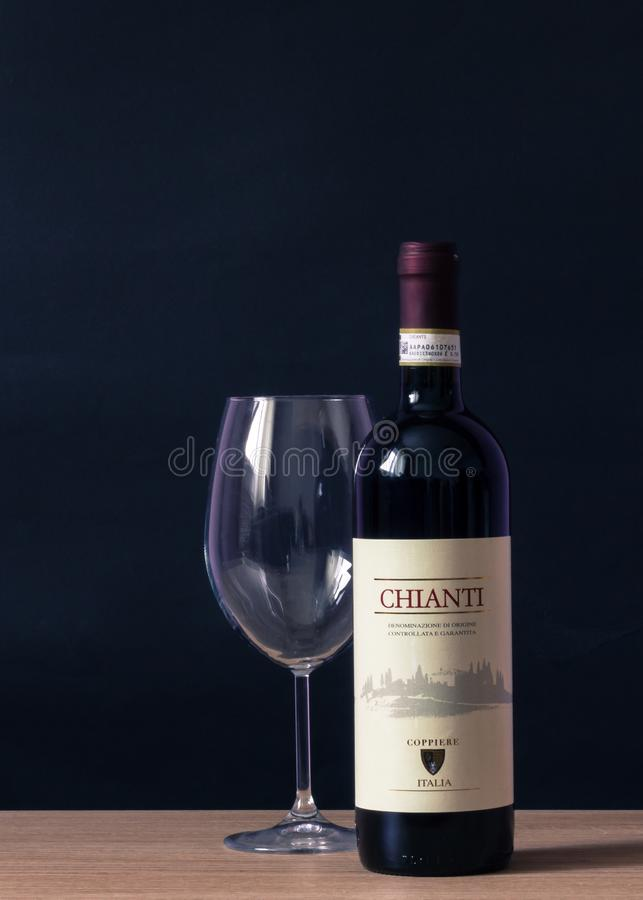 Chianti Labeled Bottle and Clear Long Stem Glass on Table stock photography