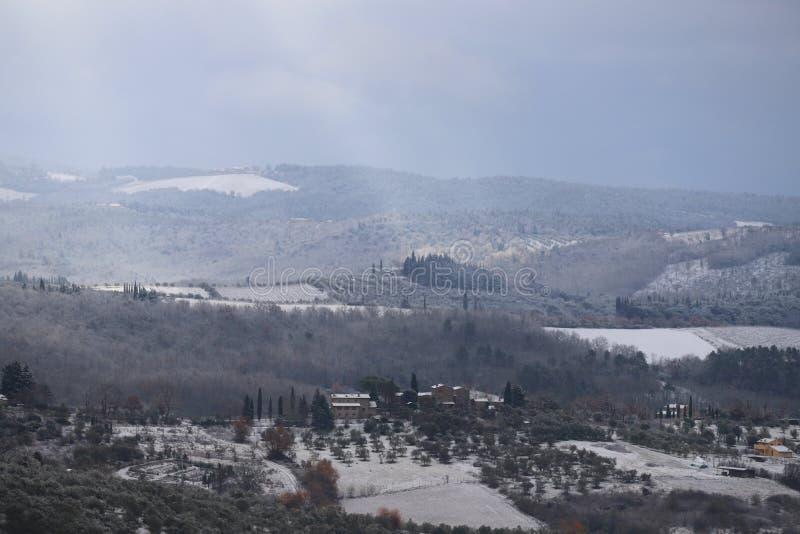 Chiantilandskapet i de Tuscan kullarna efter ett vintersnöfall fotografering för bildbyråer