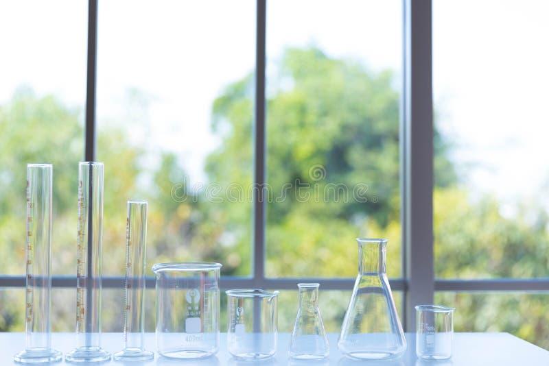 Chiara cristalleria scientifica, la dimensione differente della vetreria per laboratorio, becher o boccette sulla tavola bianca fotografie stock libere da diritti