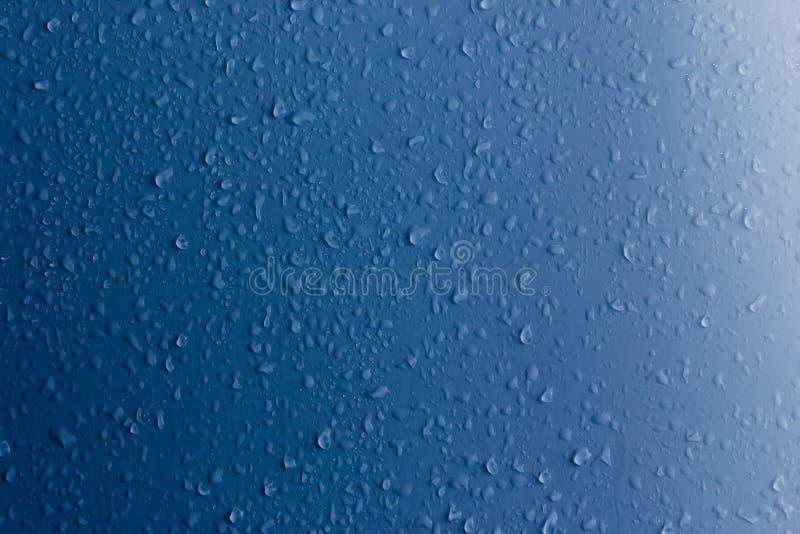 Chiare gocce di acqua su una superficie blu sottragga la priorit? bassa immagini stock