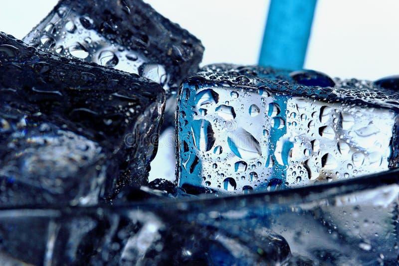 Chiari cubetti di ghiaccio di fusione in bicchiere d'acqua con le gocce closeup immagini stock libere da diritti