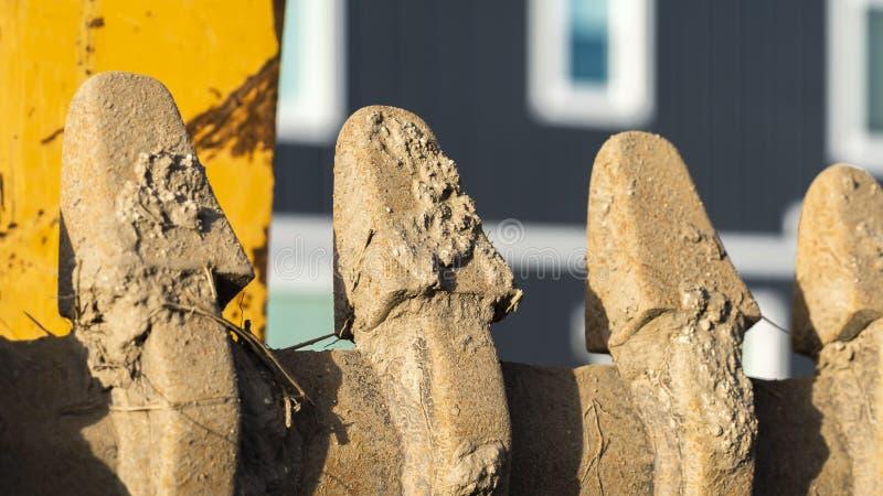 Chiari denti del secchio di panorama di un escavatore giallo ad un cantiere un giorno soleggiato fotografie stock libere da diritti