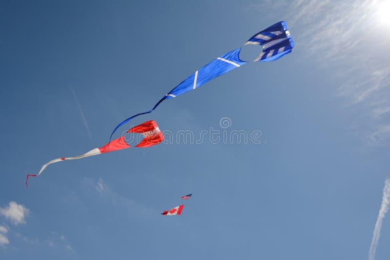 Chiaro cielo blu riempito con differenti aquiloni variopinti Uno è un aquilone canadese della bandiera immagine stock