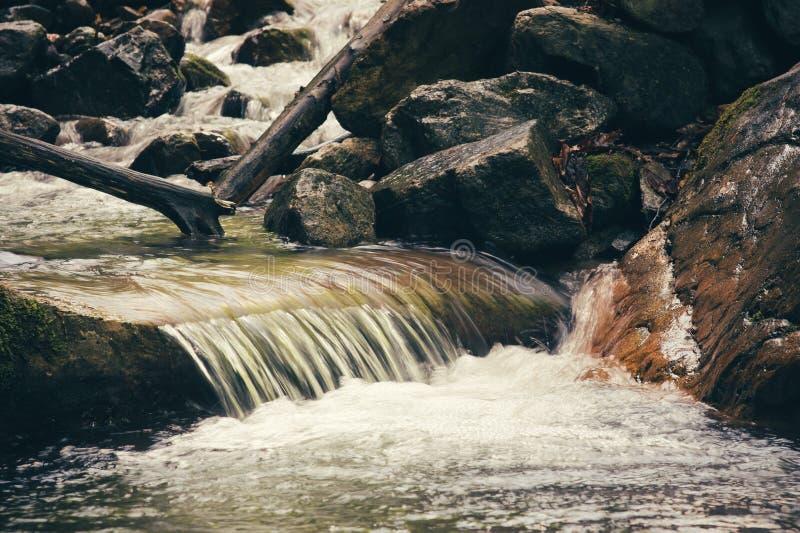 Chiaro fiume della corrente dell'acqua nel paesaggio delle montagne fotografie stock