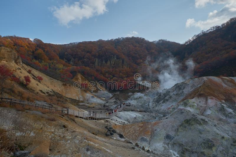 Chiaro gas dello zolfo e del cielo blu che cuoce a vapore fuori dalla terra a Noboribetsu Jigokudani o dalla valle dell'inferno n immagini stock libere da diritti
