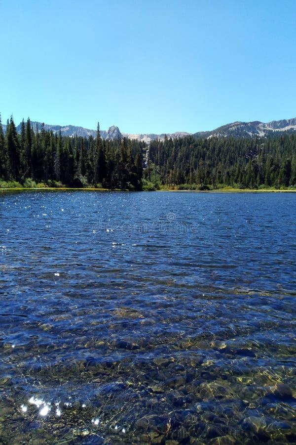 Chiaro livello del lago nelle montagne un giorno soleggiato fotografia stock libera da diritti
