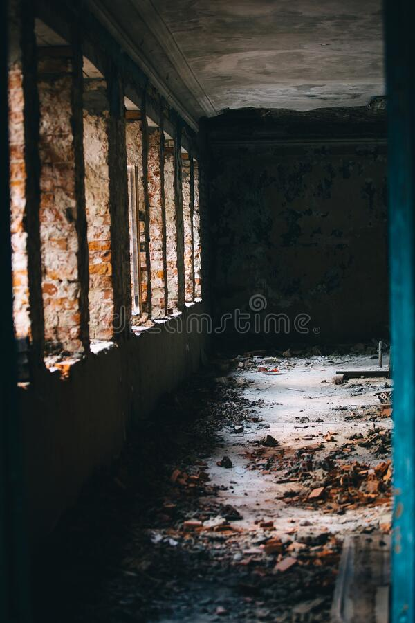 Chiaroscuro from a row of Windows in an old dilapidated building. An intimidating view inside a ghostly building royalty free stock photos