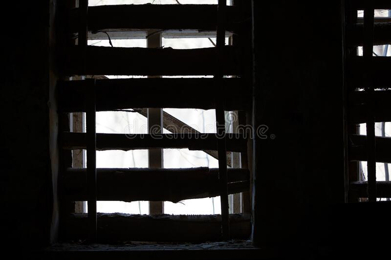 Chiaroscuro from a row of Windows in an old dilapidated building. An intimidating view inside a ghostly building stock photos