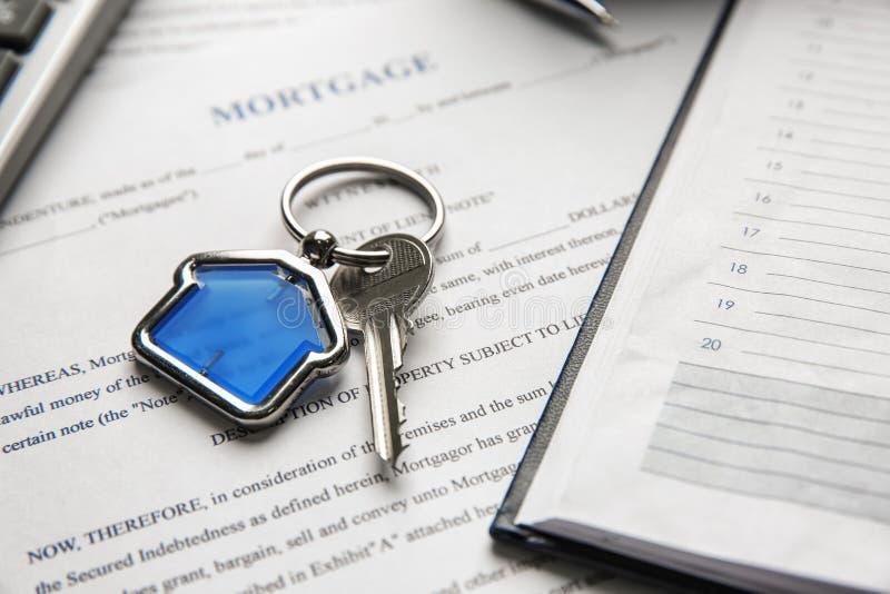 Chiave con il ninnolo nella forma della casa e dell'organizzatore personale sul contratto di ipoteca fotografia stock