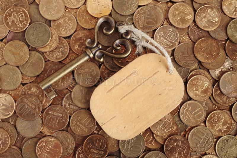 Chiave con un'etichetta sulle monete fotografia stock libera da diritti