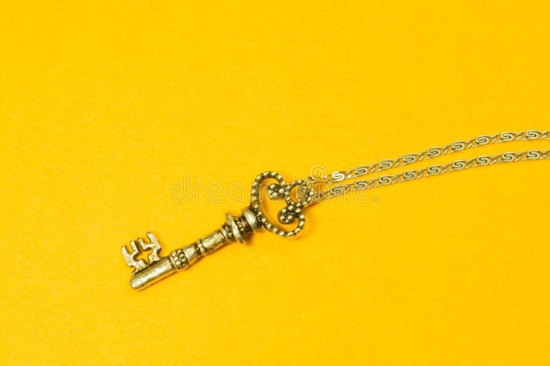 Chiave d'annata con la catena d'argento isolata su fondo giallo immagini stock