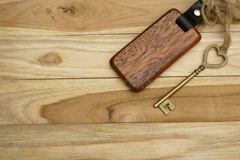 Chiave d'annata della casa con l'anello portachiavi domestico di legno sul fondo di legno del bordo, concetto della proprietà, sp immagine stock