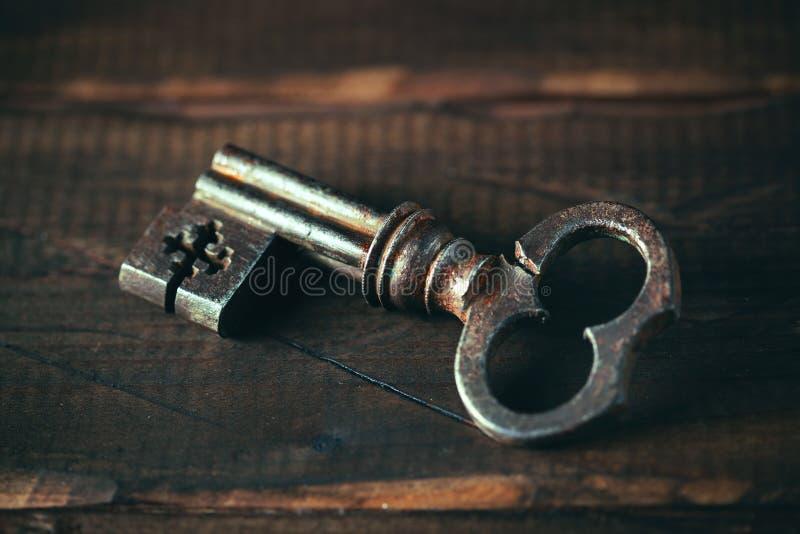 Chiave d'annata su un vecchio fondo di legno approssimativo immagini stock libere da diritti