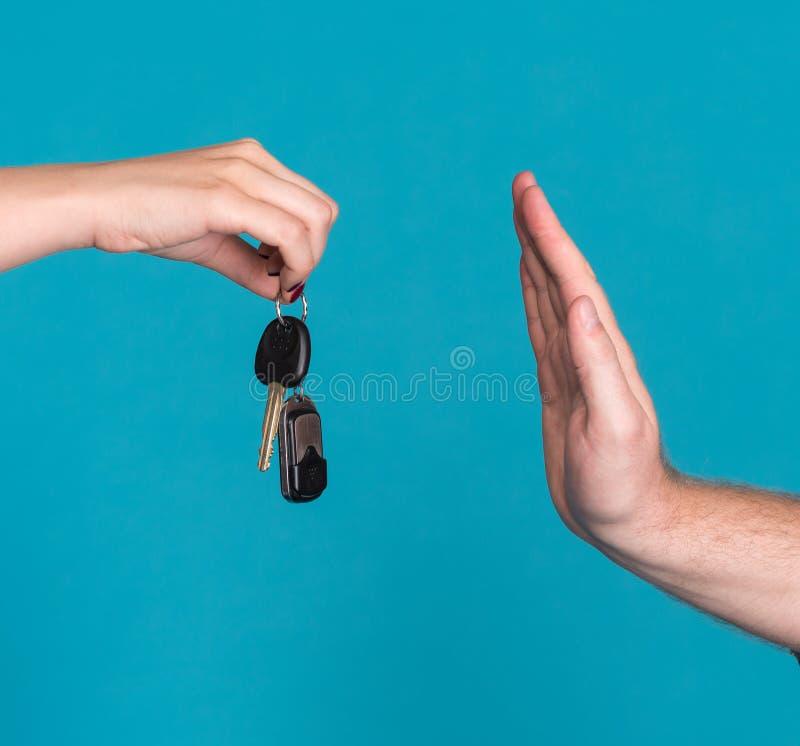 Chiave dell'automobile della tenuta della donna, uomo che solleva mano in un gesto di arresto fotografie stock libere da diritti