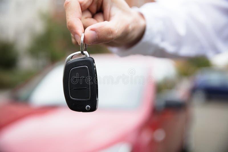 Chiave dell'automobile della tenuta della mano del ` s della persona fotografia stock