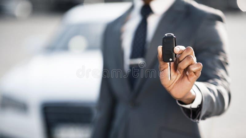 Chiave dell'automobile di rappresentazione dell'uomo d'affari contro l'auto di lusso fotografie stock libere da diritti