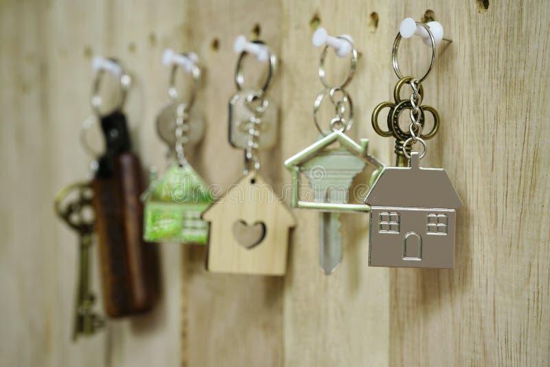 Chiave della Camera con l'anello portachiavi domestico di legno che appende sul fondo di legno del bordo, concetto della propriet immagini stock libere da diritti