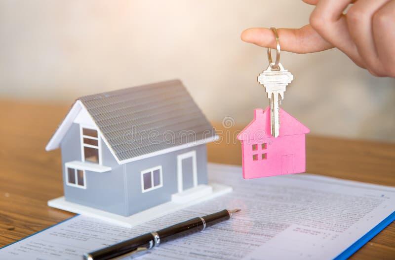 Chiave della casa della tenuta dell'agente immobiliare al suo cliente dopo la firma dell'accordo di contratto in ufficio, concett immagine stock