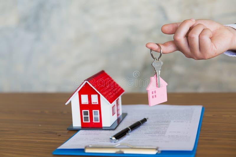 Chiave della casa della tenuta dell'agente immobiliare al suo cliente dopo la firma dell'accordo di contratto in ufficio, concett fotografia stock