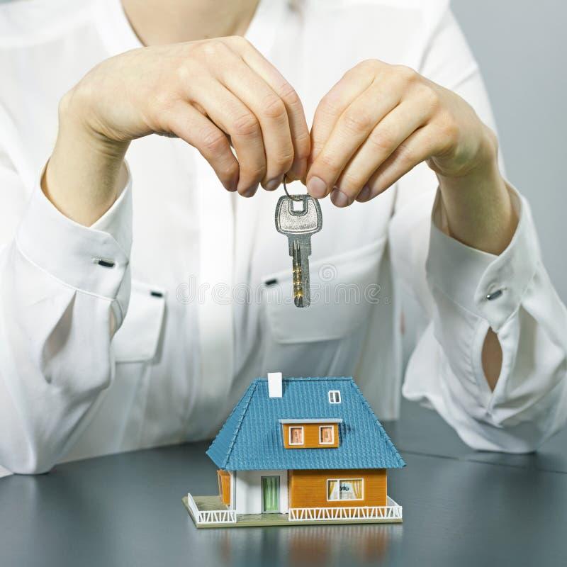 Chiave della tenuta dell'agente immobiliare sopra il modello della casetta immagini stock