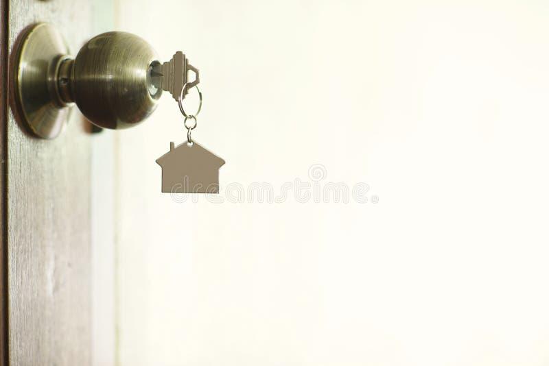 Chiave domestica con il keychain in buco della serratura, concetto della casa della proprietà immagine stock libera da diritti
