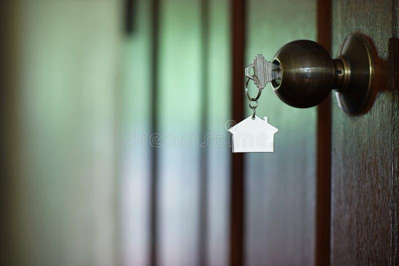 Chiave domestica con il keychain in buco della serratura, concetto della casa della proprietà immagini stock