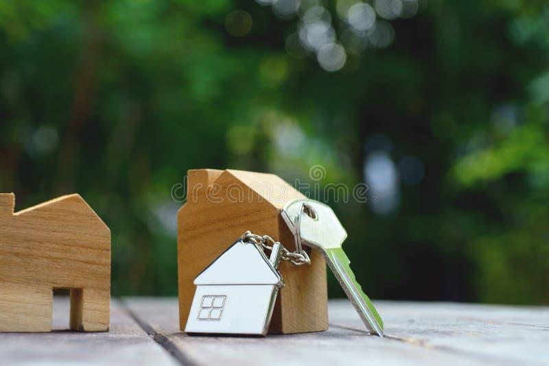 Chiave domestica con il keychain della casa su fondo di legno d'annata, concetto della proprietà immagini stock libere da diritti