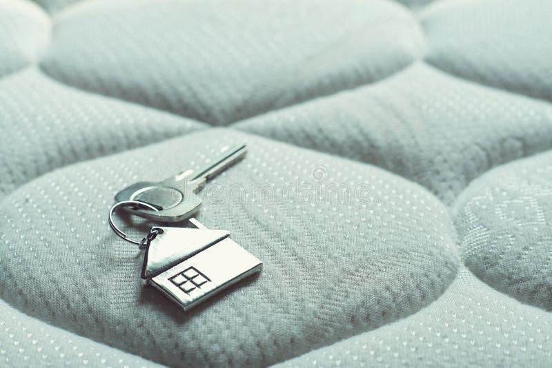 Chiave domestica con il keychain sul letto, concetto della casa della proprietà fotografia stock libera da diritti