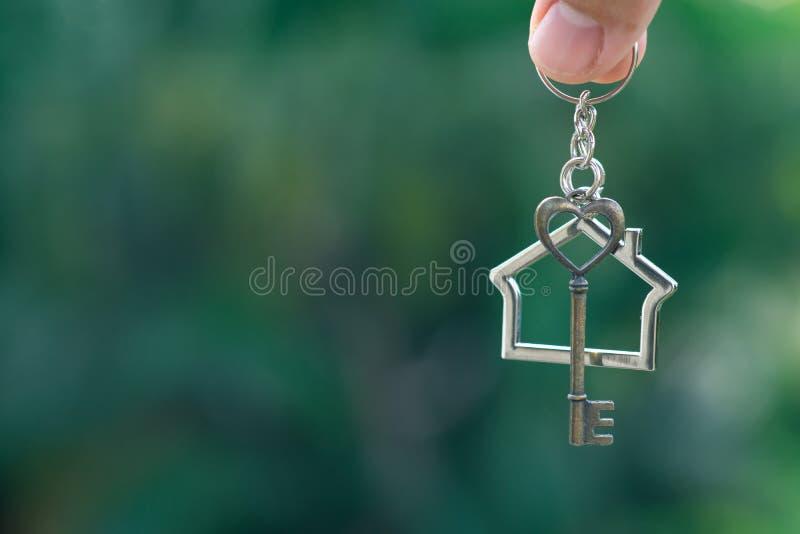 Chiave domestica con l'anello portachiavi della casa che appende con il fondo verde del giardino fotografia stock libera da diritti