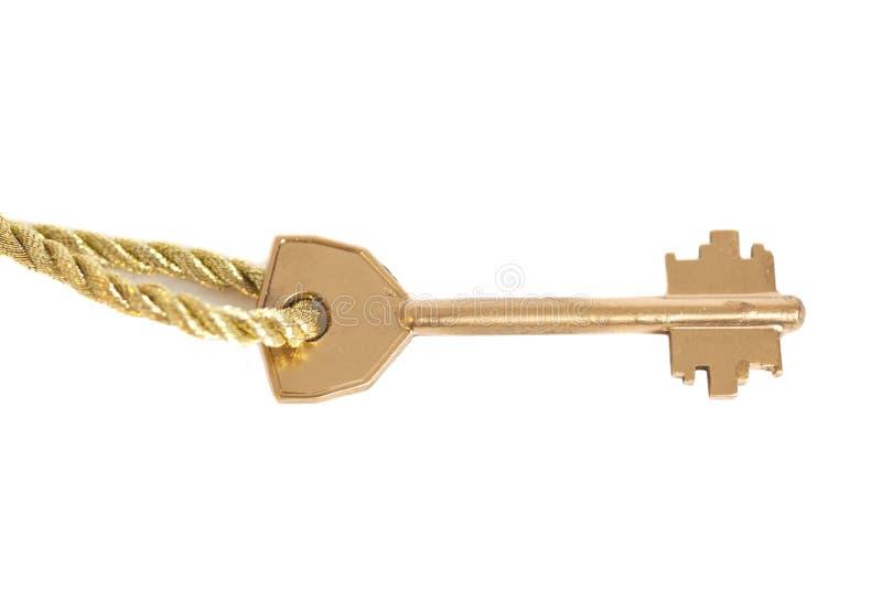 Chiave dorata che appende sulla catena dell'oro immagine stock
