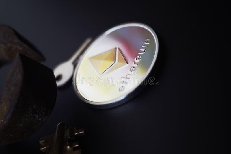 Chiave dorata della moneta Sheeny di Ethereum e pinze arrugginite fotografia stock