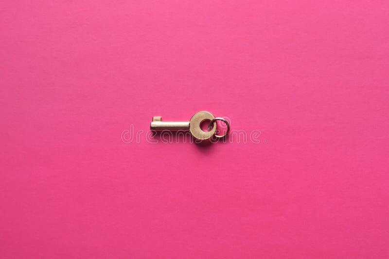 Chiave dorata su un fondo rosa fotografia stock