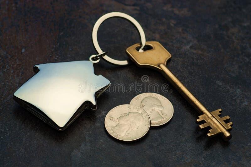 Chiave e keychain sotto forma di una casa che mette su fondo di marmo con due monete fotografie stock