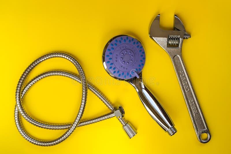 Chiave inglese del metallo, nuova testa di doccia e tubo flessibile su un fondo giallo Testa di doccia tenuta in mano con con il  fotografia stock libera da diritti