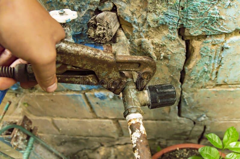 Chiave nella riparazione a mano scandagliante di un rubinetto di acqua fotografia stock