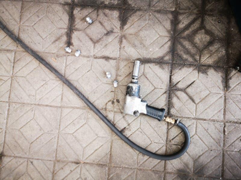 Chiave pneumatica con un tubo flessibile lungo che si trova sul pavimento delle mattonelle di pietra, vista superiore fotografia stock libera da diritti