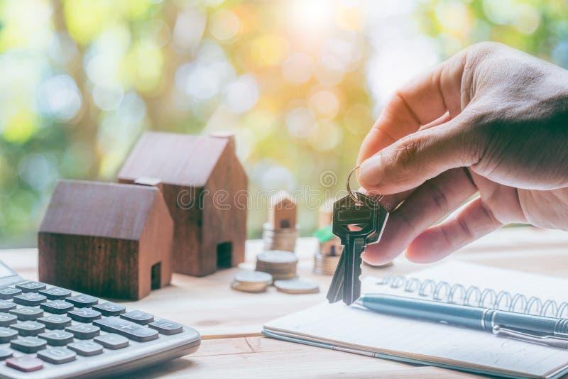 Chiave sicura della casa della tenuta della mano del giovane, agente immobiliare immagine stock