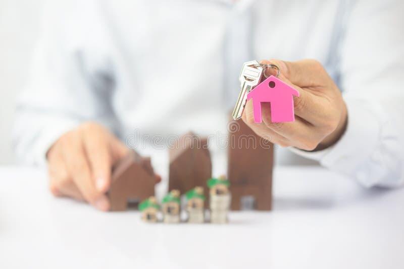 Chiave sicura della casa della tenuta della mano del giovane, agente immobiliare immagini stock libere da diritti