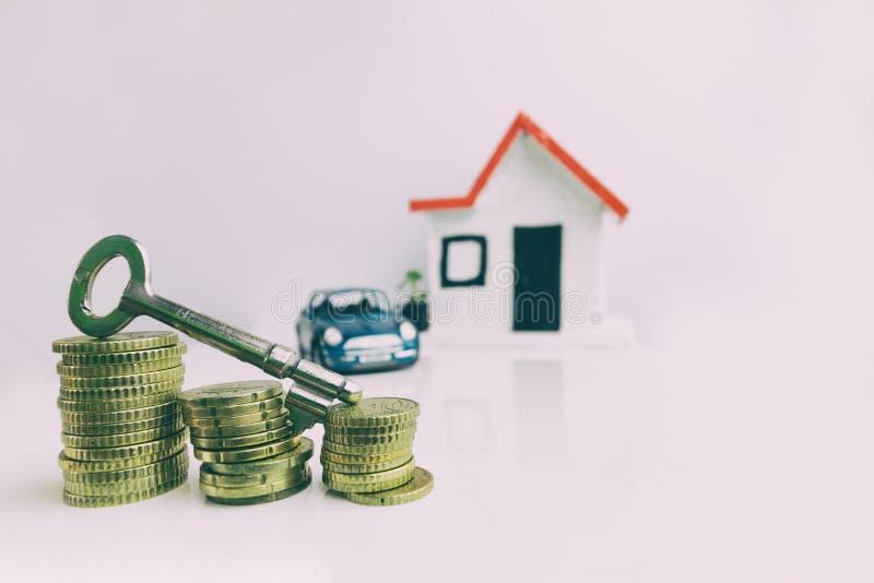 Chiave sopra una pila di monete con una casa e un'automobile vaghe sui precedenti: bene immobile, proprietà, ipoteca, concetto fotografia stock libera da diritti