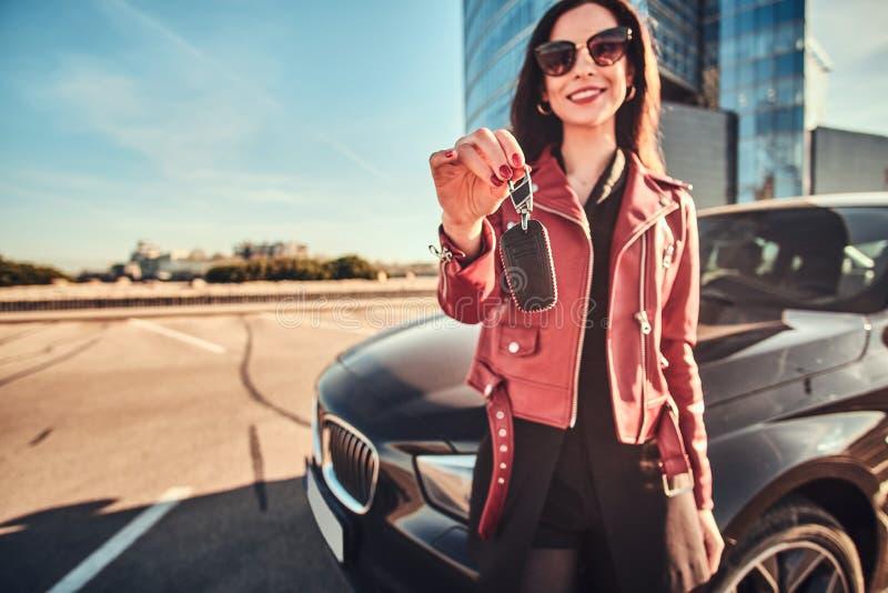 Chiave sorridente felice della tenuta della donna per l'automobile, che è behide lei immagine stock