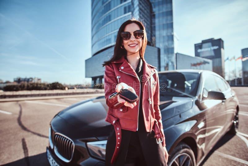 Chiave sorridente felice della tenuta della donna per l'automobile, che è behide suo, come questo è il regalo per qualcuno fotografia stock libera da diritti