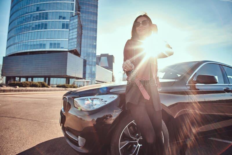 Chiave sorridente felice della tenuta della donna per l'automobile, che ? behide suo, come questo ? il regalo per qualcuno fotografia stock