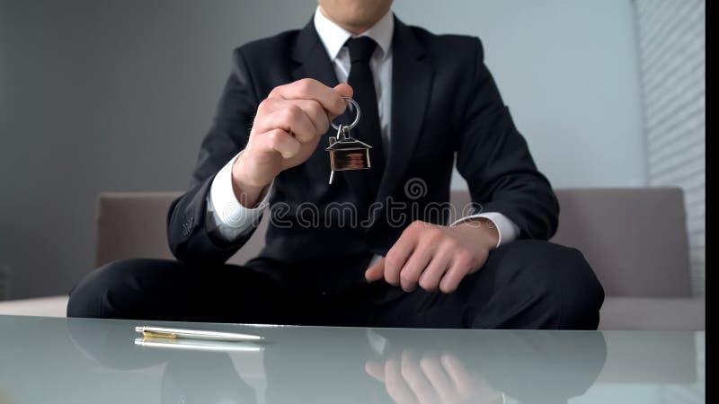 Chiavi della tenuta dell'uomo ricco dall'appartamento o dall'ufficio, iniziante nuova attività fotografia stock libera da diritti