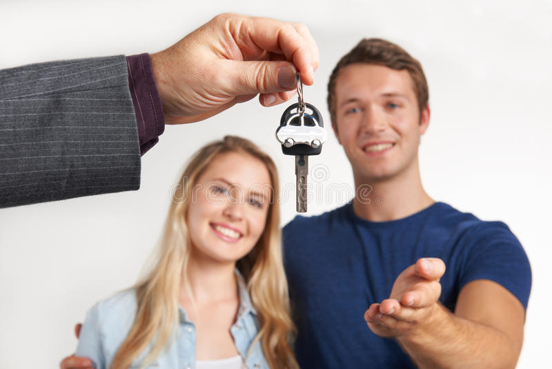Chiavi di consegna del commerciante per la nuova automobile alle giovani coppie fotografia stock